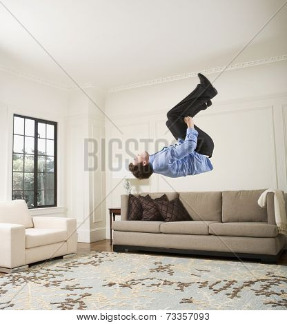 Hispanic businessman doing flip in livingroom