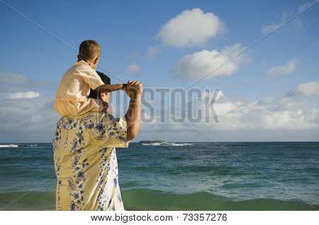 Pacific Islander father with son on shoulders at beach