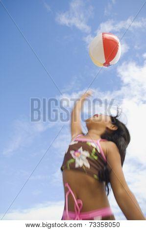 Pacific Islander girl playing with beach ball