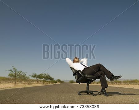 African businessman sitting in middle of road