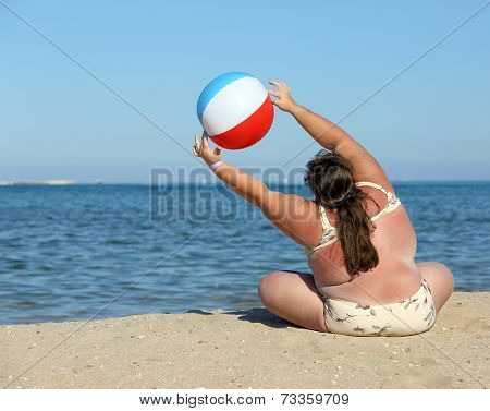 overweight woman doing gymnastics with ball on beach