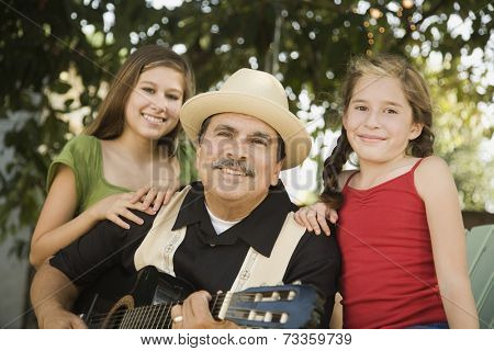 Hispanic father playing guitar for daughters