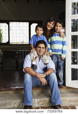 Hispanic family hugging in doorway