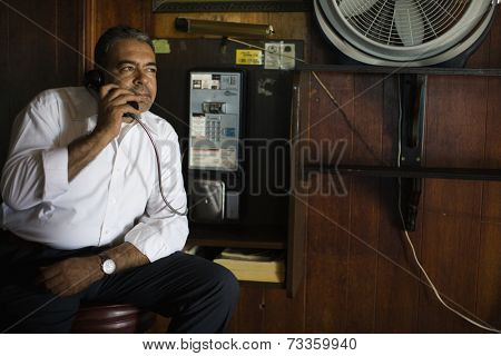 Hispanic man talking on pay telephone