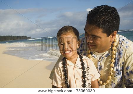 Pacific Islander father and son at beach