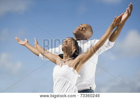 Multi-ethnic couple with arms raised