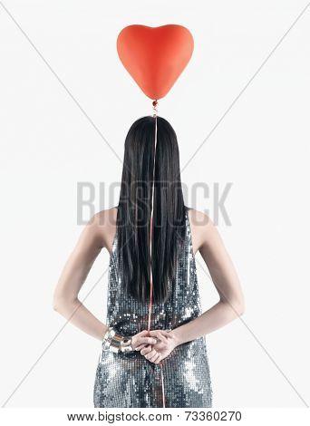 Pacific Islander woman holding heart-shaped balloon