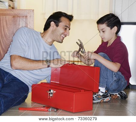 Hispanic father and son looking in tool box