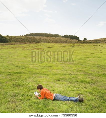 Hispanic boy playing handheld video game in field