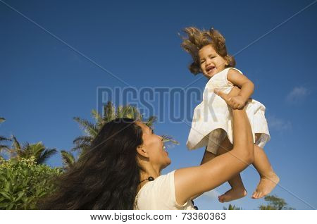 Pacific Islander mother holding daughter in air