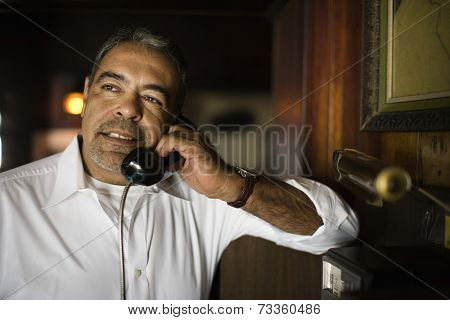 Hispanic man talking on pay telephone