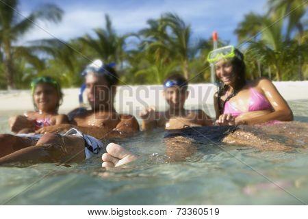 Hispanic family sitting in water