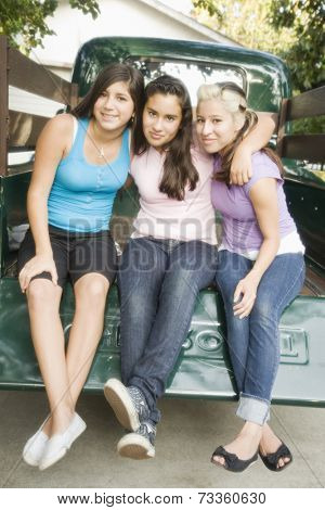 Hispanic teenaged girls sitting on truck tailgate