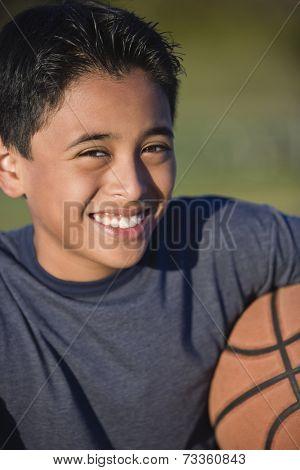 Hispanic boy holding basketball