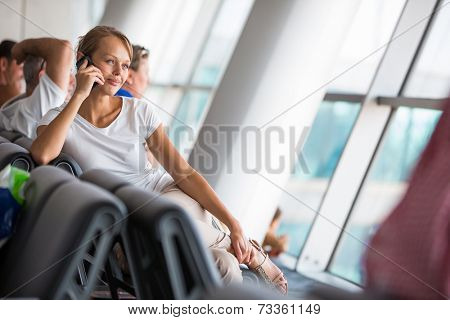 Young female passenger at the airport, about to check-in, spending last moments before getting on board on the phone, with her family