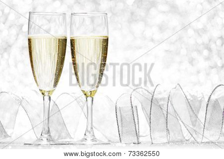 Two glasses of champagne with bow on silver background