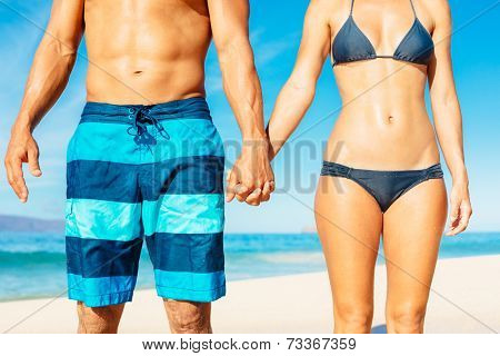 Attractive Fit Couple on the Beach in Swimwear Holding Hands