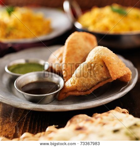 two indian samosa with mint and hot chutney