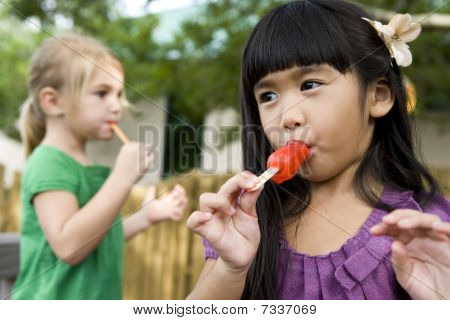 Close-up of two preschool girls eating popsicles