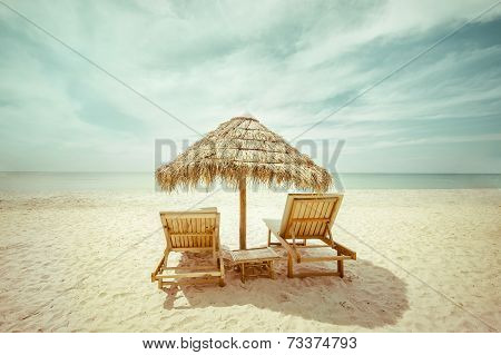 Tropical Beach With Thatch Umbrella And Chairs For Relaxation