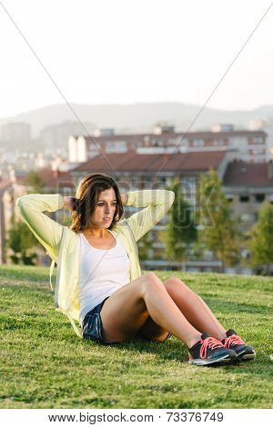 Woman Doing Situps Exercise In City Park