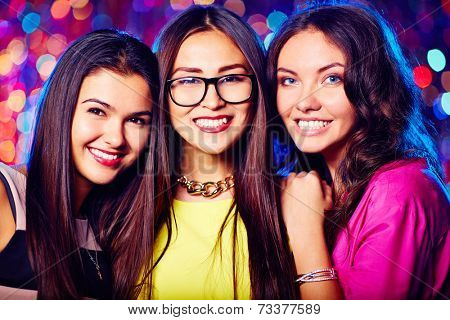Portrait of three attractive girls in nightclub