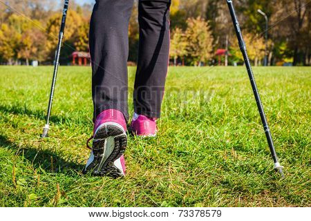 Nordic walking adventure and exercising concept - woman hiking, legs and nordic walking poles in summer nature