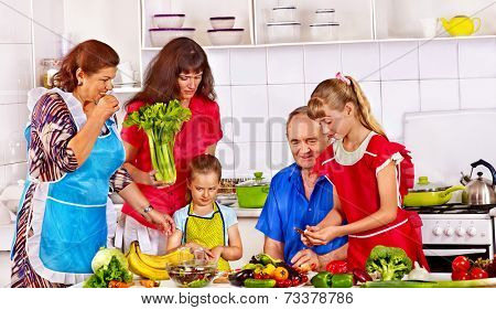 Happy family with child cooking at kitchen. Grandfather and grandmother.