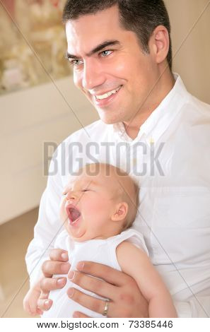 Happy father with yawning daughter on hands at home, enjoying bedtime, cheerful parenthood, love and happiness concept