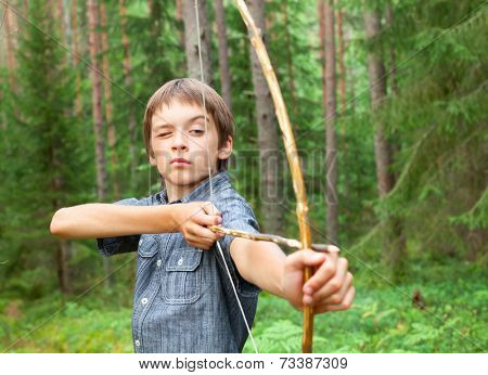 Boy aiming home-made wooden bow outdoors