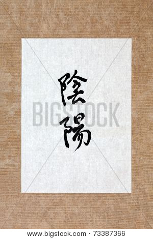 Yin and yang symbol in mandarin calligraphy script on rice paper over brown paper background. Above and below.