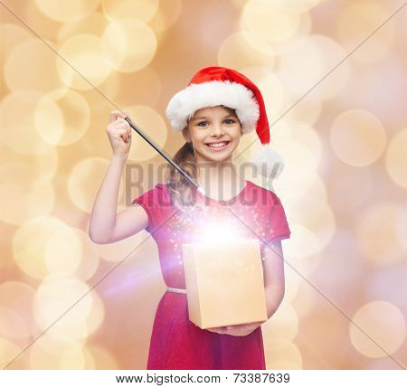 christmas, holidays, happiness and people concept - smiling girl in santa helper hat with gift box and magic wand over beige lights background