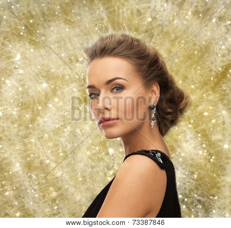 people, holidays, christmas and glamour concept - beautiful woman in evening dress wearing earrings over yellow lights background