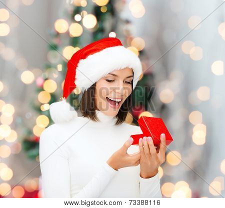 winter, happiness, holidays and people concept - smiling woman in santa helper hat with gift box over living room and christmas tree background
