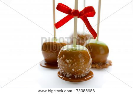 Green caramel apples with red ribbon
