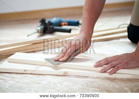 Male Hands Polishing Wooden Plank
