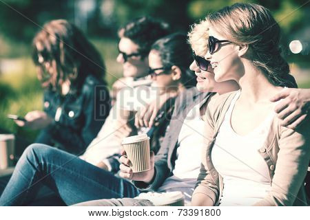 summer holidays, education, campus and teenage concept - group of students or teenagers with takeaway coffee cups hanging out