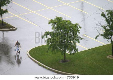 Lone Pedestrian in Empty Wet Parking Lot