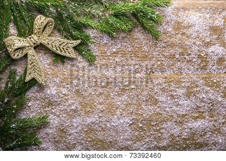 holiday decoration with snow and green branch on wooden frozen table, christmas background