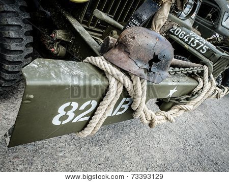 Old damaged war helmet on car bumper