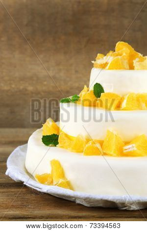 Beautiful wedding cake with oranges on  wooden background