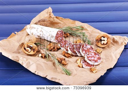 French salami and walnuts on craft paper on dark blue wooden background