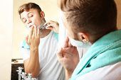 pic of shaved head  - Young man shaving his beard in bathroom - JPG