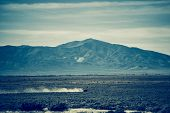 foto of truck farm  - Nevada Rural Landscape and Speeding Pickup Truck in a Distance - JPG