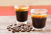 foto of mug shot  - Close up espresso shot glass and coffee bean on old wooden table - JPG