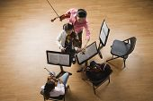 picture of pre-adolescent child  - Asian female music teacher helping student play violin - JPG
