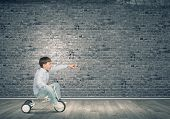 pic of tricycle  - Little joyful cute boy riding tricycle in empty room - JPG