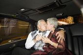 stock photo of limousine  - Well dressed senior couple kissing in limousine - JPG