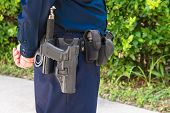 picture of officer  - Midsection of law enforcement officer in blue uniform standing guard with his weapon and baton on his belt - JPG