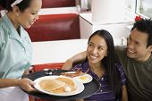 stock photo of diners  - Asian couple being served food at diner - JPG